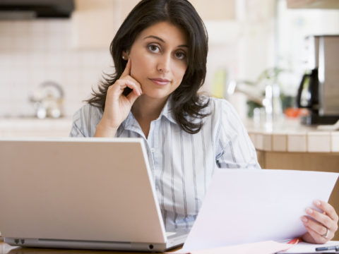 Woman On Laptop Tries To Understand Her Explanation of Benefits (EOB)